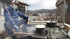 A man cooks outside the remains of his home in the tsunami-ravaged town of Kesennuma on 17 March 2011