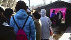 Evacuees from Fukushima prefecture wait their turn at a bath house rigged by Japanese troops on 17 March 2011
