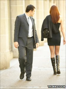 Man watching woman walk down the street