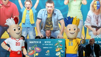 Frantisek Laurinec, UEFA Executive Committee member, holds a fake ticket for the 2012 UEFA Champions League next to mascots during the ticket launch ceremony in Kiev