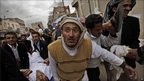 Protesters in Sanaa, Yemen, carry a wounded man, 18 March 2011