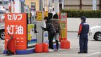 Residents fill up jerrycans with petrol in Akita (16 March 2011)