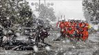 Snow falls on rubble and rescue workers in Sendai (16 March 2011)