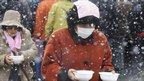 Evacuees carry bowls of pork soup from a soup kitchen back to their makeshift shelter in Minamisanriku, northern Japan