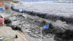 The wave from a tsunami crashes over a street in Miyako City, Iwate Prefecture in northeastern Japan after the magnitude 8.9 earthquake struck the area 11 March