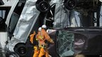 Rescue workers walk past cars upended by the tsunami at the shipping port to the east of Sendai in Miyage prefecture