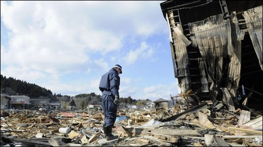 A police officer stands in silence among the debris at the destructed city of Kesennuma, northeastern Japan