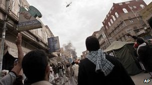 Anti-government protestors react as a military helocopter flies overhead during clashes in Sanaa, March 18, 2011