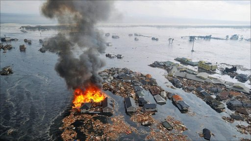 Flaming houses surrounded by debris and water following a tsunami, Sendai