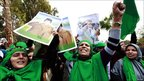Supporters of Muammar Gaddafi shout slogans during a protest outside the hotel where members of the foreign media are staying in Tripoli, Libya, 19 March 2011