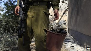 Israeli soldier gathers mortars fired on Saturday
