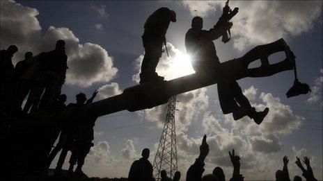 Rebels celebrate on Gaddafi tank destroyed by air strike, between Benghazi and Ajdabiya (20 March 2011)