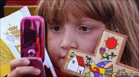child looks at mobile phone and holds crucifix
