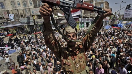 A Yemeni army officer reacts holding up his AK-47 as he and other officers join anti-government protestors in Sanaa, Yemen (21March 2011)