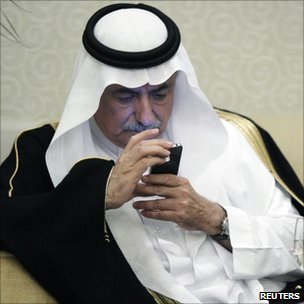 Saudi Arabia's Finance Minister Ibrahim al-Assaf looks at his iPhone during a financial conference in Riyadh