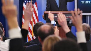 Hands raised at a White House press conference