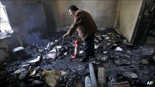 A Syrian man damps down with a fire extinguisher a burned court room in the southern city of Deraa.