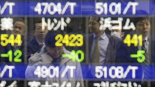 Pedestrians reflected on a stock quotation board at a security company window in Tokyo
