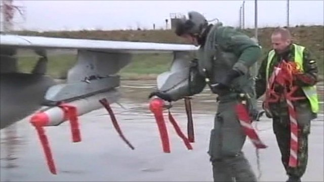 Pilot and another man checking missiles on jet fighter