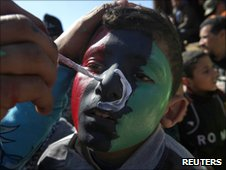 Anti-government demonstrator paints the colours of the Kingdom of Libya flag on the face of a child in Benghazi, pictured 28 Feb