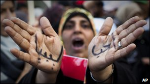 A Libyan woman reacts with her hands written on them in Arabic &quot; I love Libya&quot; 