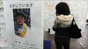People look at posters about missing people in Miyagi prefecture (23 March 2011)