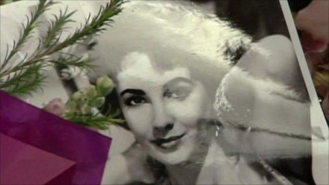 Flowers surround a photo of Elizabeth Taylor