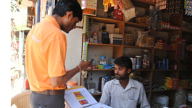 Sales representative taking an order from a shopkeeper