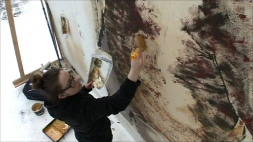 A backstage worker paints the scenery at the Royal Opera House