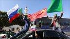 Supporters of Col Muammar Gaddafi wave flags in Tripoli, Libya (24 March 2011)