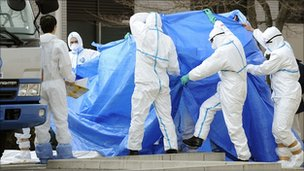 Workers who stepped into radiation-contaminated water during Thursday's operation at the Fukushima Daiichi nuclear plant, are shielded with tarps before receiving decontamination treatment at a hospital in Fukushima