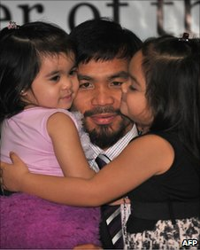 Boxer Manny Paquaio holds his daughters Queen Elizabeth (l) and Princess (r)