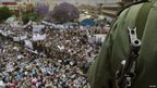 An armed policeman watches a pro-government rally in Sanaa, Yemen (25 March 2011)