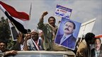 Supporters of Yemeni President Ali Abdullah Saleh on a road sign in Sanaa (25 March 2011)