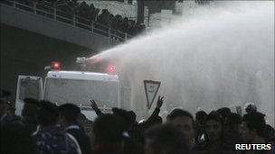 Protesters demonstrate for political reform in front of a police water cannon in Amman (25 March)