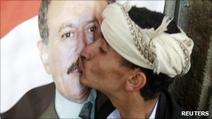 A supporter of President Saleh kisses a poster of him during a rally to show support at the Tahrir Square in Sanaa March 25, 2011