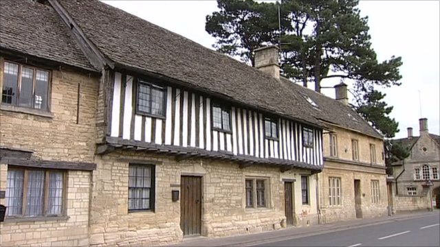 Cotswold stone houses by road in Gloucestershire