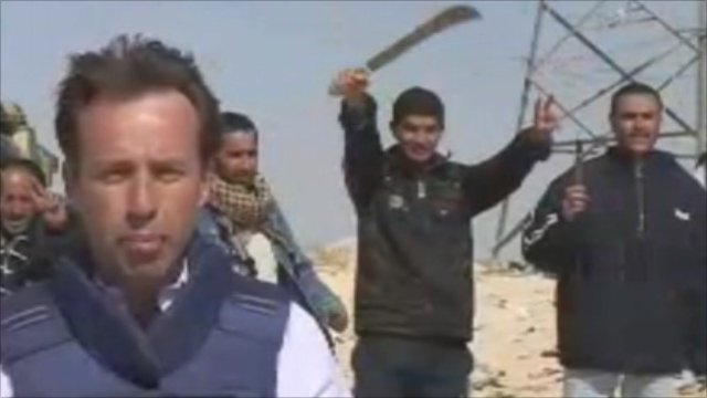 BBC correspondent Ben Brown stands as rebel waves machete in the air