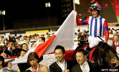 Jockey Mirco Demuro celebrates aboard Victoire Pisa