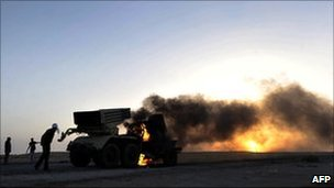 Libyan rebels walk past a burning multi-rocket launcher at sunset outside the oil rich town of Ras Lanuf, 27 March 2011