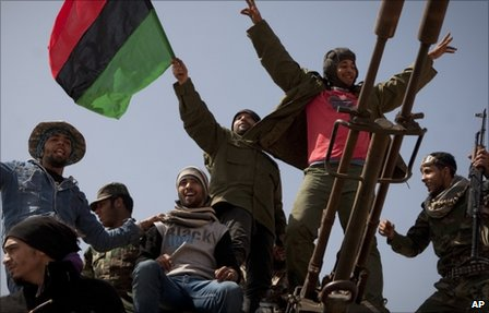 Libyan rebels jubilate on the front line outside of Bin Jawaad, 150km east of Sirte, central Libya (25 March 2011)