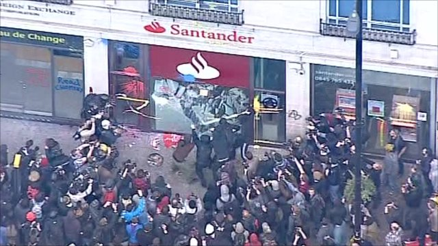 People breaking a glass window of a bank on Oxford Street in central London