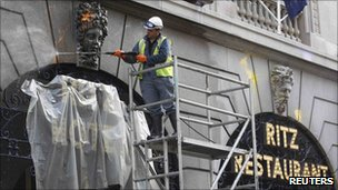 A worker removes paint from the facade of the Ritz Hotel after riots, pictured 28 March
