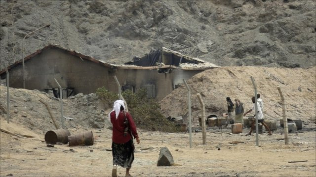 Tribesman walks at the site of an explosion at a bullet factory in the southern Yemeni town of Jaar