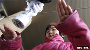 8-year-old Ayami Suzuki is tested for possible nuclear radiation, Fukushima, northern Japan March 28, 2011