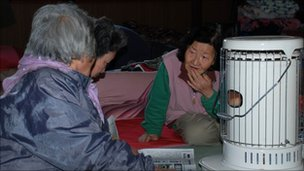 Elderly women sit around the only space heater in an evacuation centre in Iwate prefecture in northeastern Japan on 29 March 2011