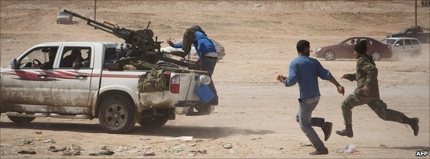 Rebels flee from shelling by pro-Gaddafi forces near Bin Jawad, 150km east of Sirte, Libya, 29 March 2011