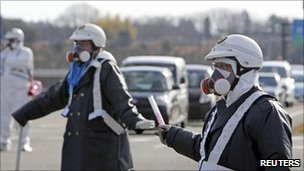Police wearing respirators guide people away from the Daiichi nuclear plant on 12 March 2011