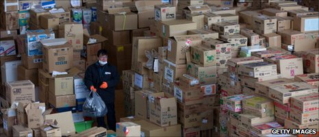 A man walks through boxes of emergency relief supplies in Onagawa