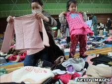 A girl and her mother try secondhand clothes, donated for relief supplies at a shelter at Onagawa